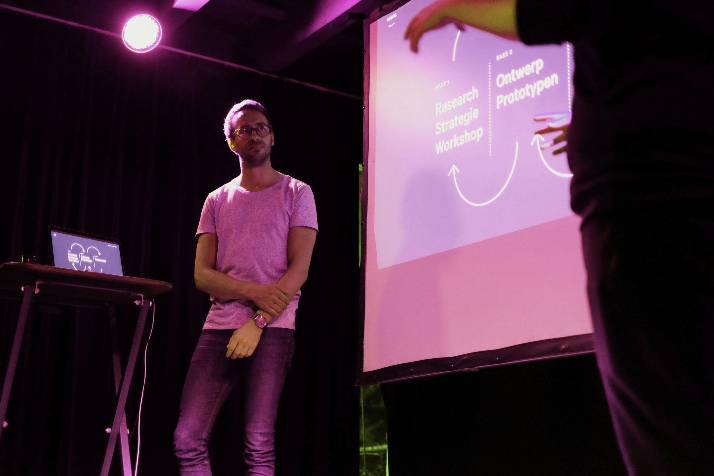 Twee personen op podium spreken over Naam's werkwijzes