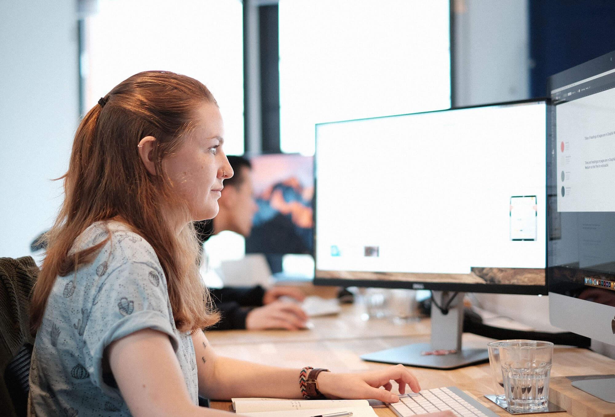 Ontwerper achter een iMac werkt aan een website ontwerp