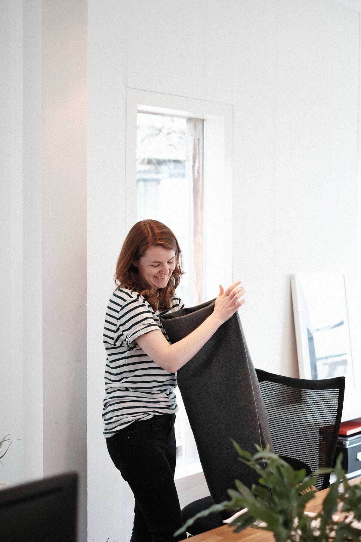 Vrouw vouwt een dekentje in kantoor