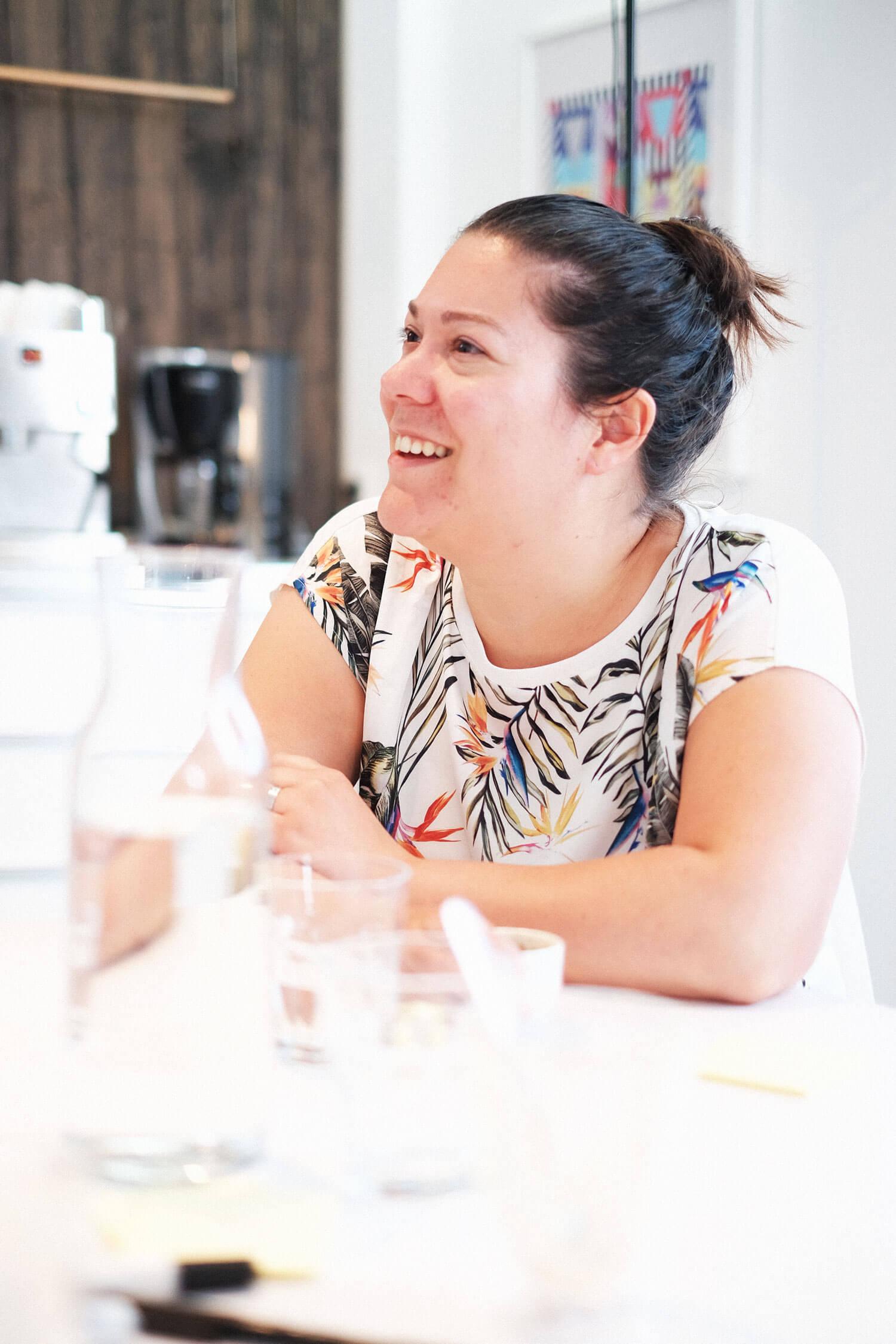 Vrouw zit aan tafel en lacht
