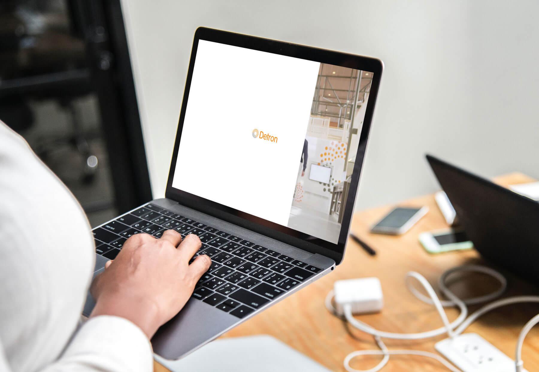 Vrouw houdt een laptop vast met daarop de vacature website ontwerp voor Detron