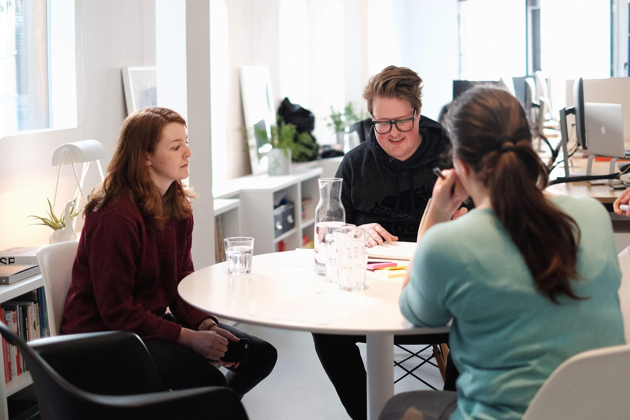 3 mensen hebben een design vergadering aan tafel