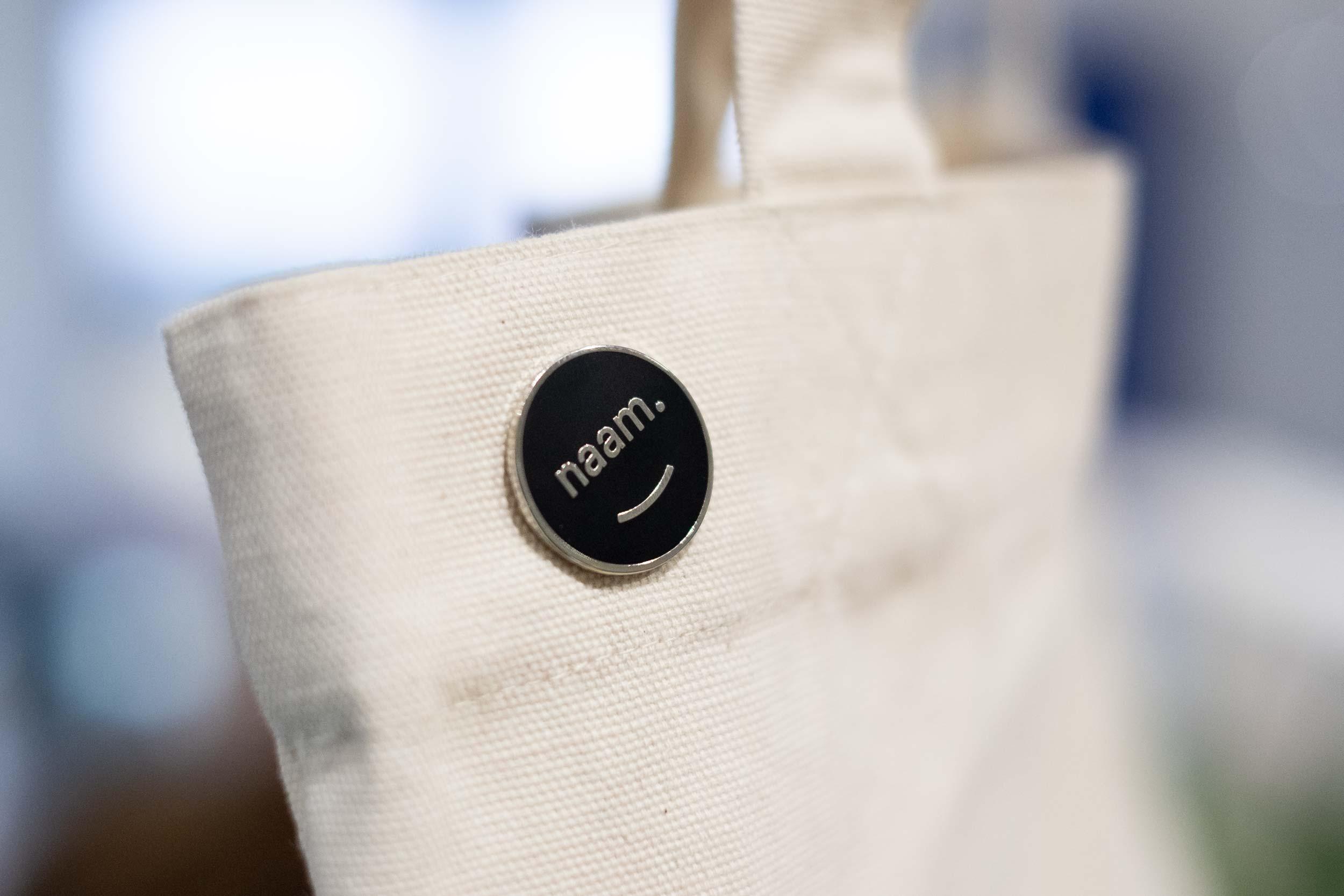 Een canvas tote tas met een Naam logo emaille button.