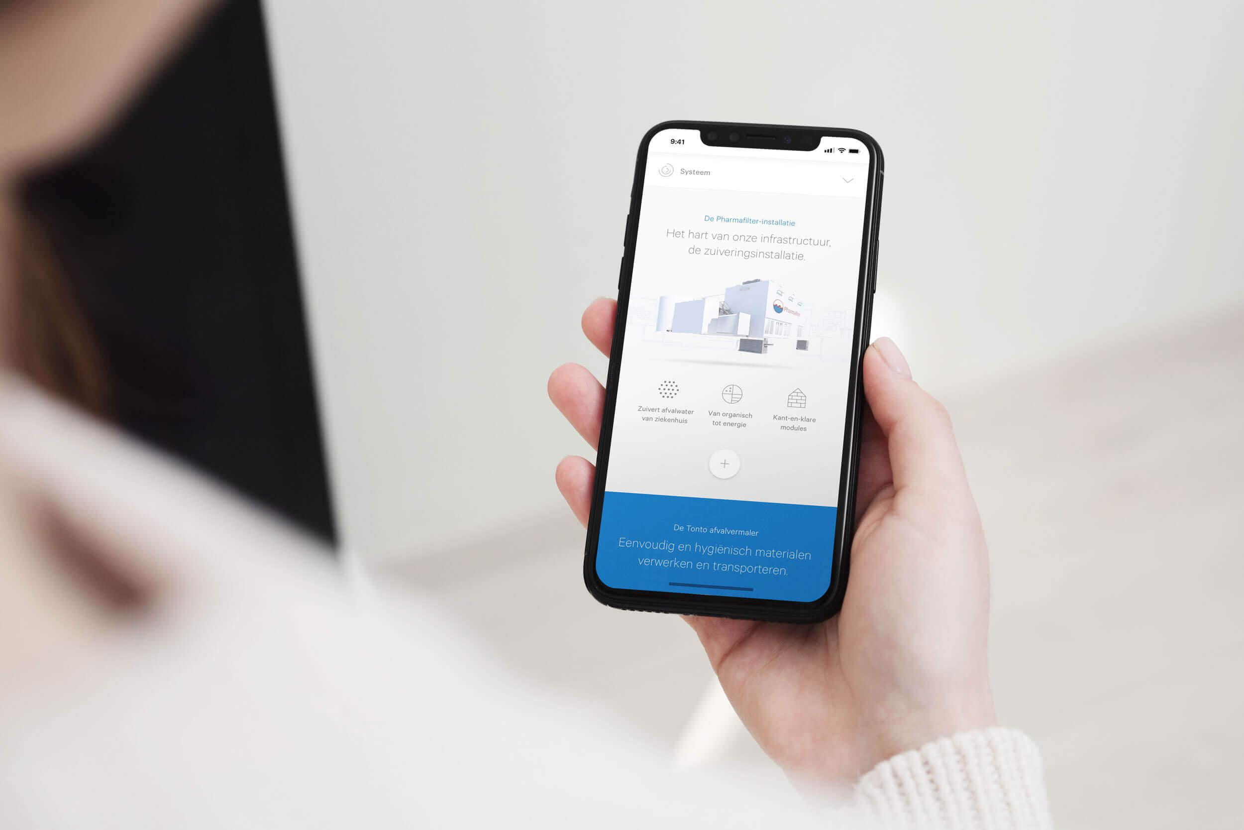 Vrouw houdt een telefoon vast met daarop het Pharmafilter website ontwerp