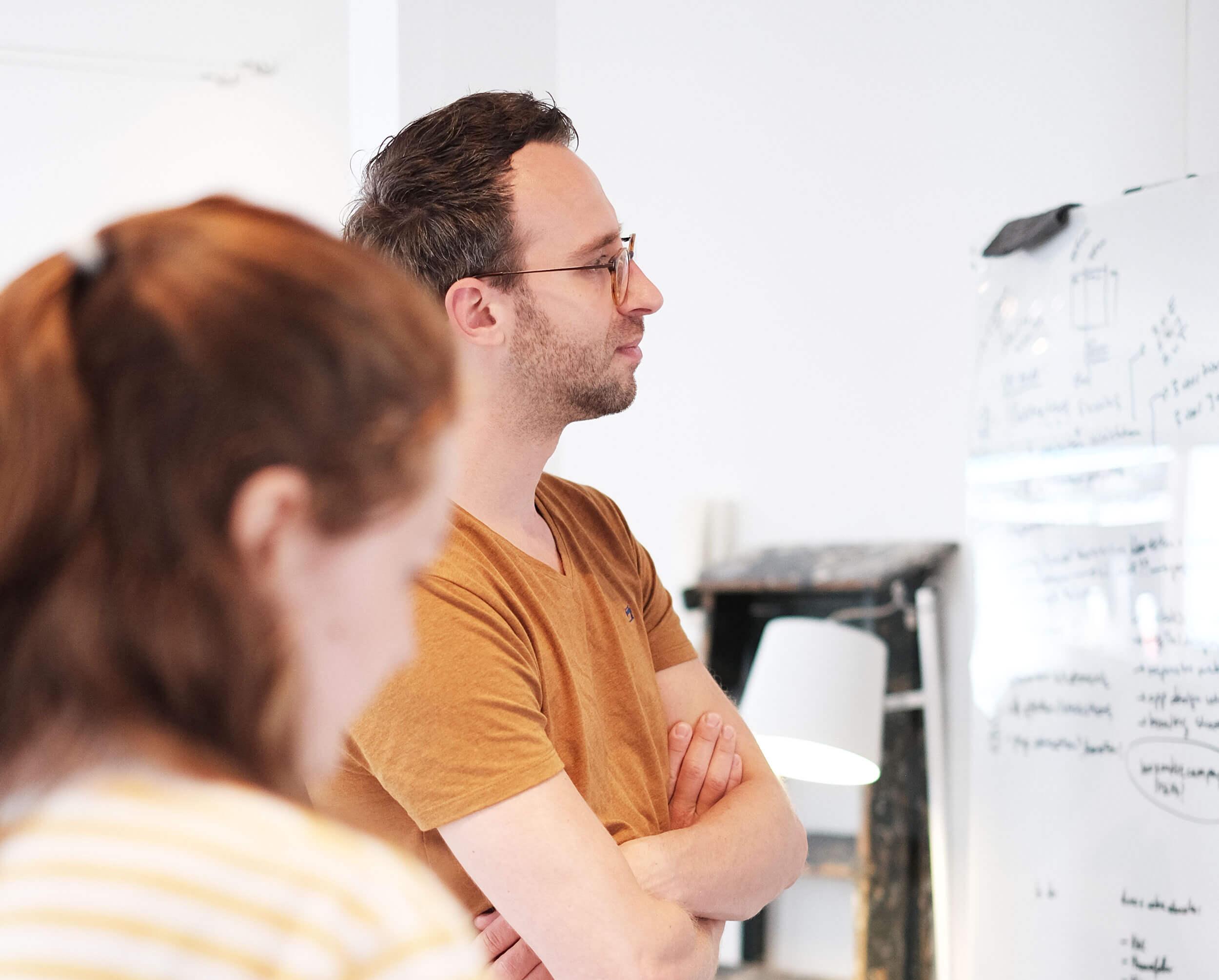 Joris en Ellie kijken naar een strategisch plan op het whiteboard